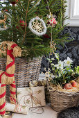 Christmas tree decorated with straw figurines, basket of hellebores and gifts