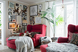 Red armchair below antlers and framed photos on walls