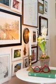 Hyazinthe, Kerze, Buch und Brille auf Beistelltisch vor gerahmten Fotos