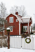 Falu-red Swedish house in snowy garden
