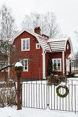 Rotes Schwedenhaus mit schneebedeckter Garten