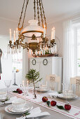 Chandelier above festively decorated dining table