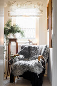 Grey sheepskin blanket on armchair in front of window