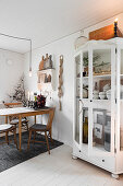 Old glass-fronted cabinet in festively decorated dining room