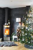Kaminofen und Weihnachtsbaum im Wohnzimmer mit Schieferplatten als Wandverkleidung