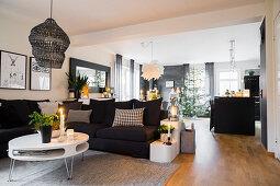 Polstersofa und runder Couchtisch in offenem Wohnraum mit Weihnachtsdekoration