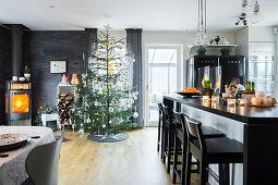 Elegante Kücheninsel, im Hintergrund Weihnachtsbaum und Kaminofen in offenem Wohnraum