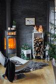 Kaminofen und Holzlager im Wohnzimmer mit Schieferplatten als Wandverkleidung