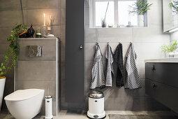 Badezimmer mit grauen Wandfliesen, Blick auf Toilette und Waschtisch