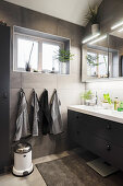 Blick auf Waschtisch im Badezimmer mit grauen Wandfliesen