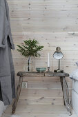 Old, weathered stool used as bedside table against board wall