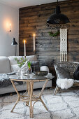 Wicker furniture and beige sofa in front of rustic board wall