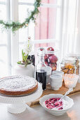 Cake on cake stand and bowl of quark and fruit next to window