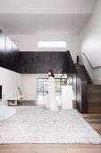 Elegante, minimalistische Halle mit Treppenaufgang, Frau in weißem Kleid