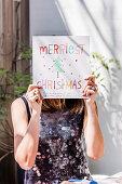 Frau hält Weihnachtsgruß vor ihr Gesicht