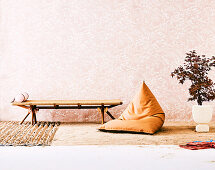 Day bed, beanbag and Japanese maple tree against a wallpapered wall