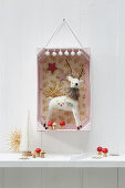 3D diorama of Christmas decorations in pink-painted fruit crate hung on wall