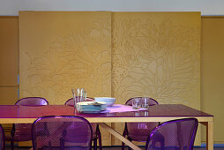 Dining table and purple acrylic chairs in front of sliding doors with relief decoration