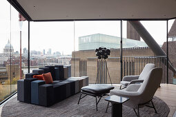 Modern living room with panoramic view of city through glass walls