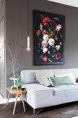 Graues Polstersofa mit Kissen, Beistelltisch, Pendelleuchte und Blumenbild