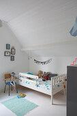 Weißes Kinderbett im Kinderzimmer im Dachgeschoss