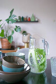 Bowls in earthy shades next to carafe of water, cucumber and mint