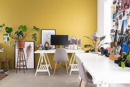 Zwei Schreibtische auf Möbelböcken an gelber Wand
