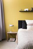 Gelbe Wand hinter dem Bett im Schlafzimmer