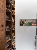 Offenes Holzregal für Gläser und Geschirr neben einer Wandnische