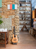 Guitar leaning against stone wall in artist's apartment