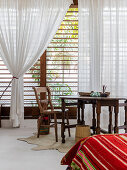 Blick vom Bett auf den Holztisch vorm Lamellenfenster