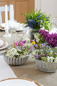 Spring flowers in vintage cake tins decorating table