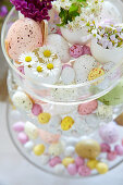 Easter eggs and flowers on glass cake stand