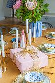 Rosafarbenes Geschenk, Kerzen und Blumen auf gedecktem Tisch