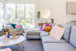 Simple gray sofa with colorful pillows in front of the window front