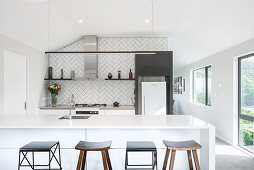 Kitchen counter with integrated sink and bar stools in open-plan kitchen