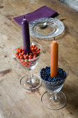 Candles in wine glasses filled with rose hips and viburnum berries