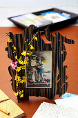 Photo of children in unusual frame decorated with sprig of flowers