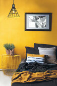 Bed and metal bedside table against yellow wall