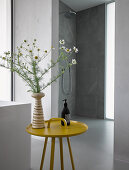 Vase of flowers on yellow side table in modern bathroom