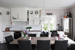 Large dining table and upholstered chairs in white country-house kitchen