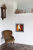 Old armchair next to fireplace integrated into wall