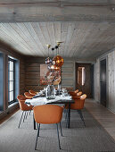 Cognac-brown chairs around set dining table in log cabin