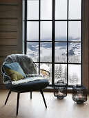 Armchair in front of floor-level window with view of winter landscape