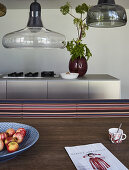 View across dining table to modern kitchen island