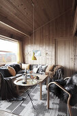 Fur blanket and cushions in seating area of wood-panelled chalet living room
