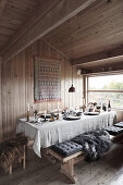 cushions and fur blanket on bench next to dining table set with linen cloth in chalet dining area
