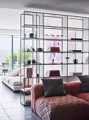Floor-to-ceiling, transparent shelf as a room divider in an open living space