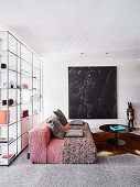 Red designer sofa, coffee table and picture in front of floor-to-ceiling, transparent shelves in open living space