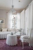 Runder Tisch mit bodenlanger Tischdecke, Stühle und Metallbett in weißem Zimmer